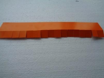 Сложить полоску по ширине пополам и сделать надрезы до линии сгиба по всей длине на расстоянии 2 см.