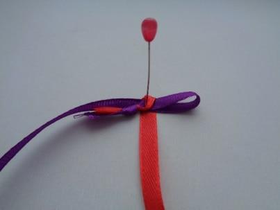 Лентой красного цвета обогнуть петельку из фиолетовой ленты.