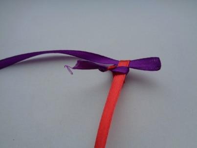 Сделать петлю из фиолетовой ленты и ввести её в петлю красной ленты. Подтянуть красную ленту.
