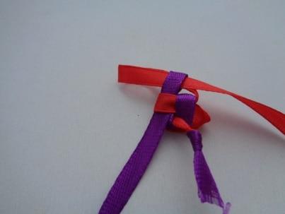 Сделать новую петлю из красной ленты и протянуть её в фиолетовую ленту. Затянуть фиолетовую ленту.