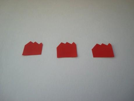 Вырезать из красной бумаги полоску длиной 1,5 см. С одной стороны полоски вырезать зубчики.